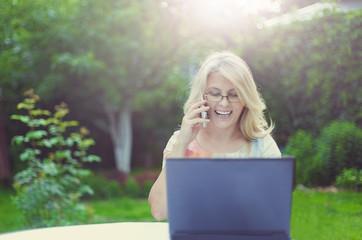 Красивая женщина за столом с ноутбуком в саду