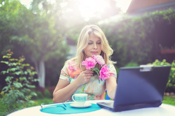 Красивая блондинка за чашкой кофе и с ноутбуком