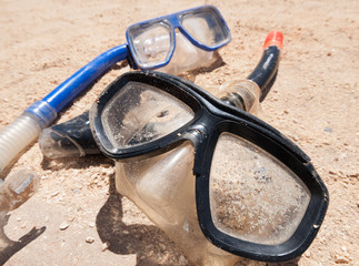 A pair of mask and snorkels on a golden sandy beach, with a beautiful shallow depth of field.