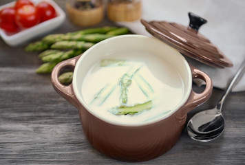Asparagus soup on wooden table