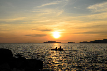 Silhouette people kayak in the sea with summer sunset sky background at Li Pe island Thailand.