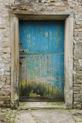 A blue weathered rustic, Old wooden farm stable door, set in a stone wall