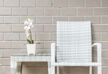 Closeup artificial plant with white orchid flower on pink flower pot on wood weave table with wood weave chair on blurred brown brick wall texture background , beautiful interior in relaxation concept