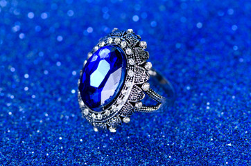 Wall Mural - Jewellery ring against blue background