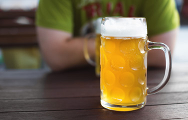 Glass of tapped craft beer. Pale ale on a pub table