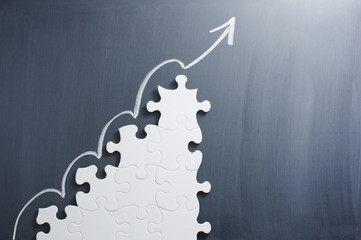 Obraz Steps shaped jigsaw puzzle and up arrow on blackboard. Concept image of making growth strategy.   - fototapety do salonu