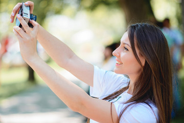 Cheerful young woman is taking selfie photo with old fashioned camera.