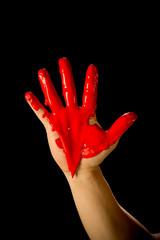 Pintura roja escurre en la mano