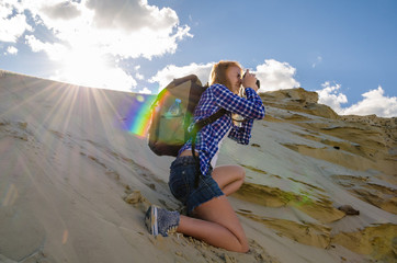 Young beautiful woman backpacker traveling and making pictures in the desert. Sandy dunes and blue sky on sunny summer day. Travel, adventure, freedom concept. Toned.
