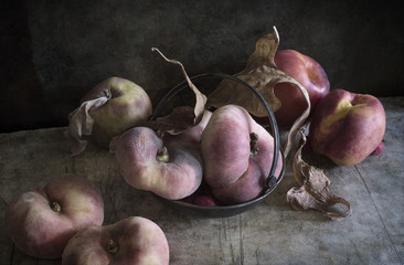 Still life with peaches, apple and dry leaves (textured for artistic effect)