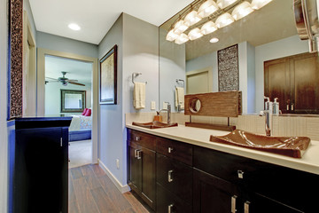 Blue and brown bathroom interior with black brown cabinets and large mirror.