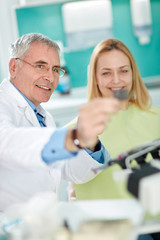 Dentist with female patient look at dental snapshot