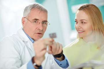 Dentist explains to female patient problem with tooth using dent