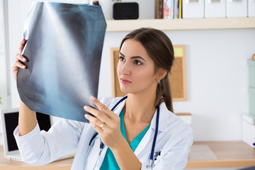 Young female medical doctor or intern looking at lungs x-ray ima