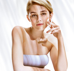 Beautiful blonde girl removing make up from her face. Youth and skin care concept