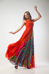 Beautiful woman in bright colorful dress dancing
