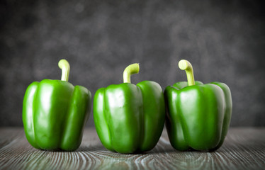 Green bell pepper on wooden board dark background front view