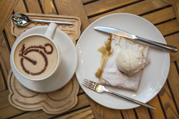 Cup of coffee and apple strudel with ice cream