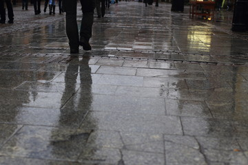 Walking along wet pavement street. Rain in the city.