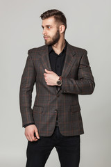 Studio portrait of handsome elegant young man in brown jacket po