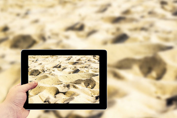 Tablet photography concept. Taking pictures on a tablet. Hills of sand on beach as desert