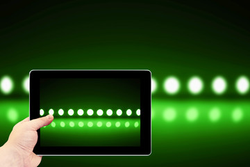 Tablet photography concept. Taking pictures on a tablet. Play of green light on defocusing blur led lamps background