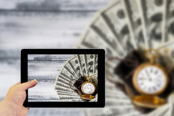 Tablet photography concept. Taking pictures on a tablet. Stack of money dollars laid out like a fan with antique gold watch on white retro stylized wood background