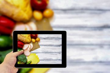 Tablet photography concept. Taking pictures on a tablet. Set of products for cooking on white vintage wooden work surface