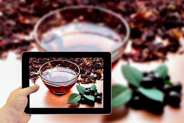 Tablet photography concept. Taking pictures on a tablet. Still life cup of black tea with mint leaves on dried karkade tea background