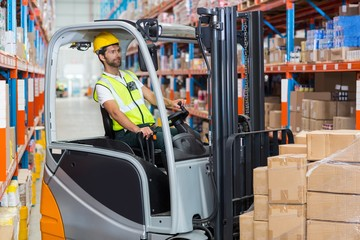 Worker is driving a pallet truck