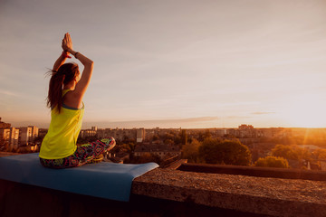 Young girl yoga on the roof. Silhouette