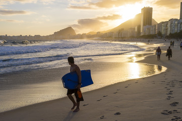 Silhouette of bodyboarder walking in front of golden sun setting behind the Rio de Janeiro skyline at the Leme end of Copacabana Beach