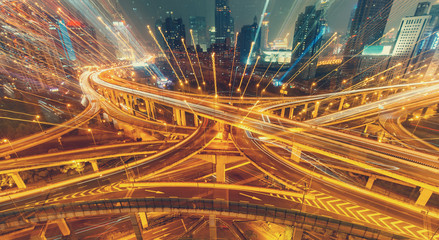View over the famous Dragon highway intersection in Shanghai, China, with traffic. Abstract nighttime skyline.