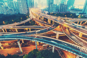 View over the famous Dragon highway intersection in Shanghai, China, with traffic. Shanghai skyline in the evening.