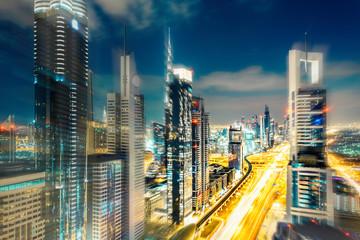 Scenic Dubai nighttime skyline with illuminated skyscrapers. Travel background.