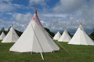 Glamping camping tipis tepees in a field on sunny day