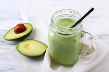 Delicious fresh avocado smoothie on white wooden background