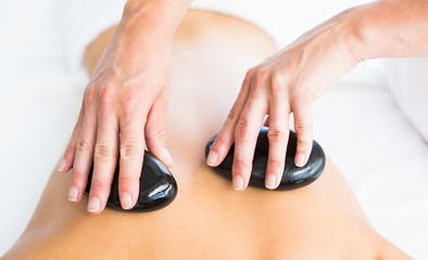 Cropped image of masseur giving hot stone massage on woman back