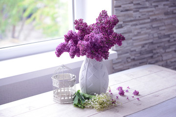 Lilac bouquet and may-lily flowers on a table