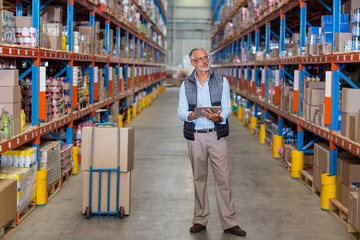 View of manager is holding a tablet and looking shelves