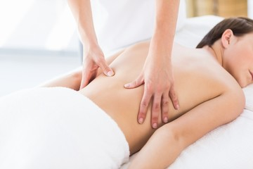 Naked woman receiving back massage