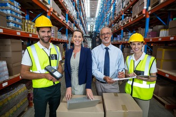 Businessmen and warehouse workers