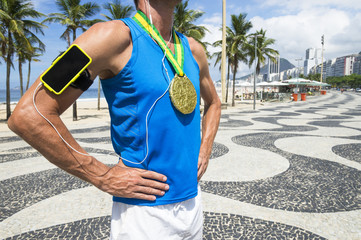 Gold medal athlete wearing mobile phone technology armband stands listening to motivational music outdoors on the boardwalk at Copacabana Beach, Rio de Janeiro, Brazil