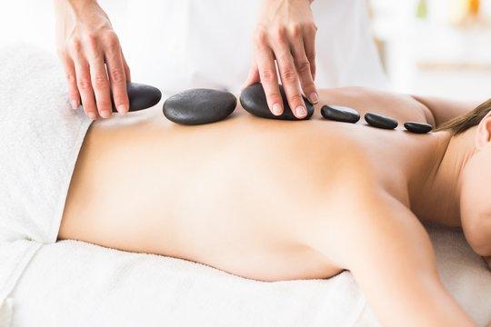 Masseur giving hot stone massage to woman