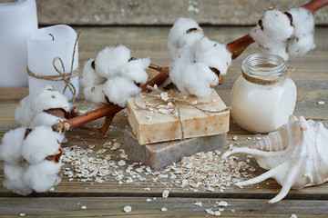 Natural handmade soap, oat flakes, cream and cotton branch on wo