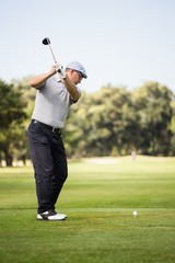 Profile view of man playing golf
