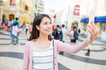 Woman taking selfie by mobile phone in Senado Square of macau