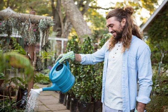 Happy gardener watering plants at community garden