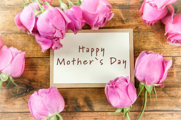 Happy Mothers Day. Fresh roses and card on wooden background