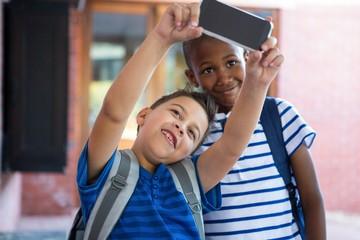 Classmates taking selfie at school corridor